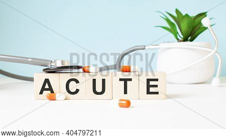 The Word Acute Is Written On Wooden Cubes Near A Stethoscope On A Wooden Background. Medical Concept