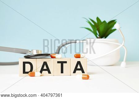 The Word Data Is Written On Wooden Cubes Near A Stethoscope On A Wooden Background. Medical Concept
