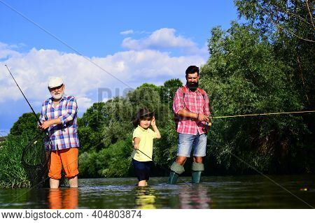 Fishing. Little Boy Fly Fishing On A Lake With His Father And Grandfather. Grandfather And Father Wi
