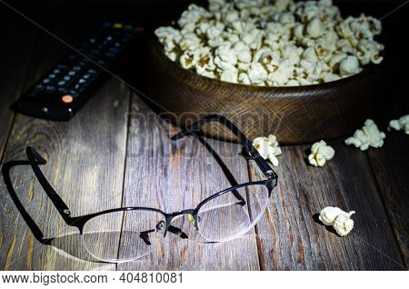 Popcorn, Tv Remote And Glasses On A Wooden Background. Night. The Concept Of Watching Movies Or Tv S