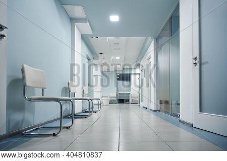 Empty Modern Hospital Corridor, Clinic Hallway Interior Background With White Chairs For Patients Wa