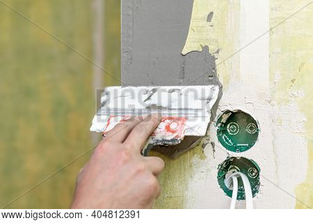 Man Is Plastering A Wall. Process Of Applying Plastic Mixture To Perforated Corners. Plastic Boxes A