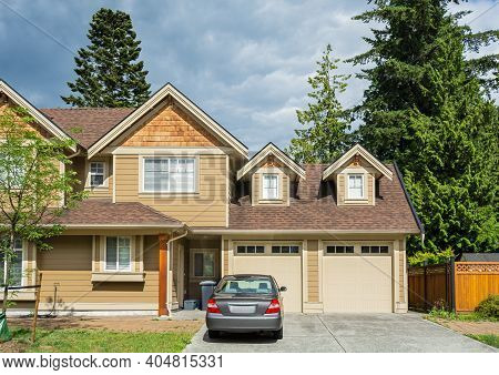 Luxury Residential House With Car Parked In Front On Cloudy Sky Background