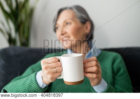 A Close-up A Mug In Hands Of A Charming Senior Mature Lady In Out Of Focus, Looking In The Window, D