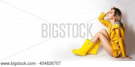 Horizontal Banner With Young Woman In Yellow Slicker And Rubber Boots Sitting Sideways . Fashion Blo
