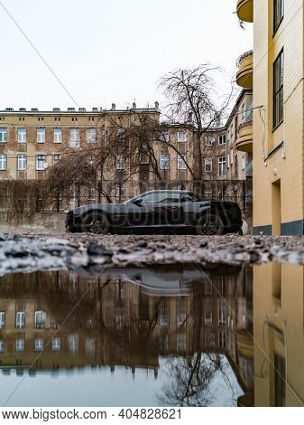 Lodz, Poland - February 23 2020 Black Camaro Reflected In Small Puddle