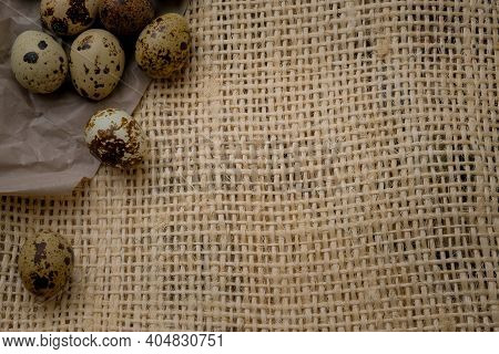 Easter Quail Eggs On Craft Paper And Rustic Burlap Background. Easter Eggs On Craft Paper And Burlap