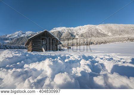 Wooden Barn Covered By Snow In Sunny Alpine Winter Landscape In Wildermieming, Tirol, Austria