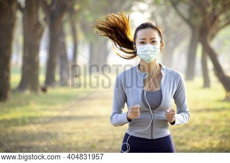 Young Woman In Face Mask And Running In The Park