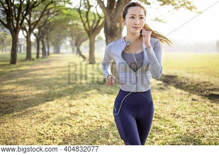 Beautiful Asian Young Woman Running In The Park At  Morning