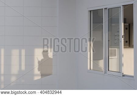 Evening Sunlight Shining Through Glass Windows Of Sentry Box With Shadow Of Security Guard Using Wal