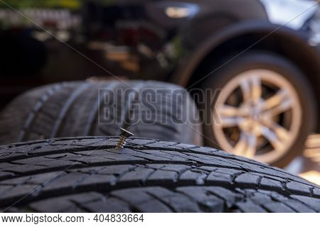 Close Up Old Tire Have Nails Nut Or Screw Drive Stuck In Side. Tire Workshop And Change Old Wheel On
