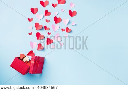 Valentines' Day Background. Red Gift Box Postcard And Paper Flying Elements Hearts Cut Greeting Gift