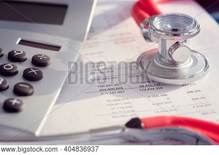 Calculator and stethoscope on financial statement concept for finance health check or cost of healthcare