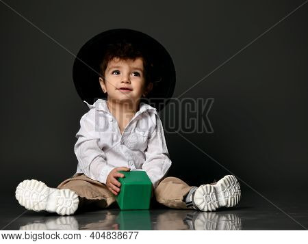 Stylish Baby Boy. Toddler Child Model Wearing Casual Apparel, Shoes And Hat Holding Toy Building Blo