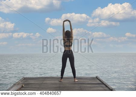 Young Healthy Woman Practicing Yoga On The Bridge In The Nature