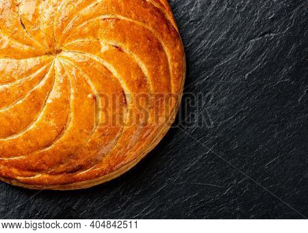 Epiphany cake or galette des rois in French on black slate background