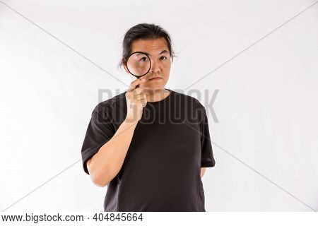 Man Holding Magnifying Glass On White Background. Man With A Magnifying Glass In Studio. Positive Cu