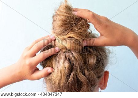 The Girl Straightens The Disheveled Bun On Her Head With Her Hands. Modern Fast Hairstyle. Blue Back