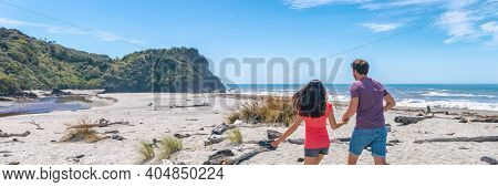 Couple walking on beach in New Zealand running on romantic travel holiday Ship Creek on West Coast, South Island of New Zealand banner.