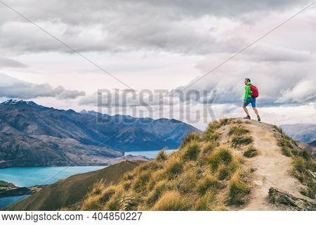 Hiking man adventure travel explorer hiker on mountain summit looking at landscape view. Hiker tramping up famous trail hike to Roys Peak on South Island, New Zealand.