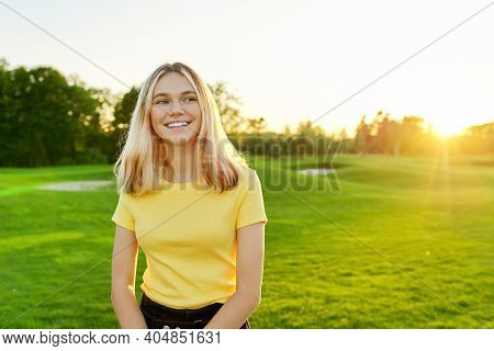 Outdoor Portrait Of Smiling Teenage Girl 16, 17 Years Old In Yellow T-shirt, On Green Sunny Lawn. Su