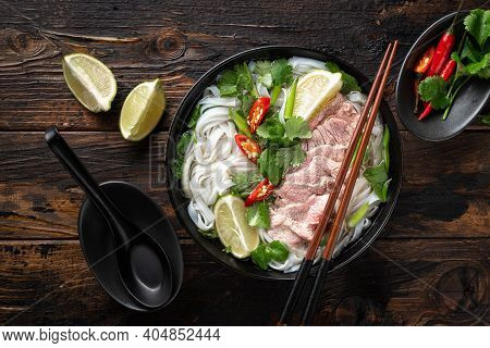 Pho Bo Vietnamese Soup With Beef And Noodles On A Wooden Background, Top View