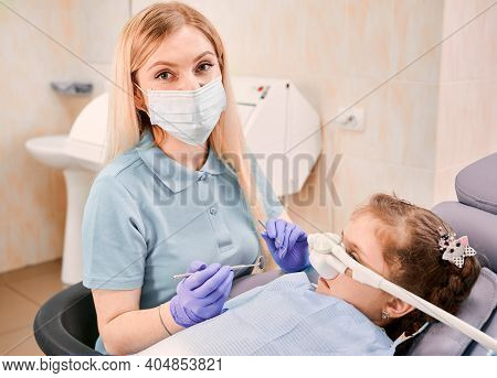 Close Up Dentist In Medical Face Mask Holding Dental Instruments While Girl Lying In Dental Chair Wi