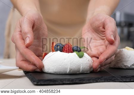 Pastry Chef Prepares Delicate Cake With Fresh Berries. Cake Anna Pavlova. Close Up