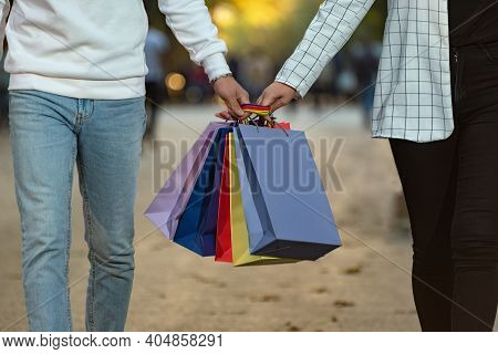 Couple In Love Carries Multi-colored Paper Shopping Bags. Shopping Together.