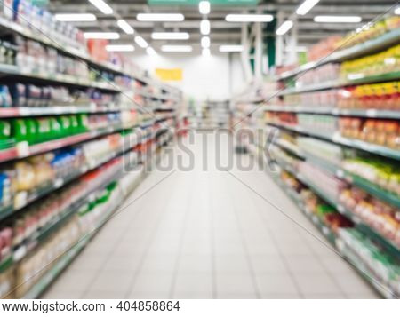 Blurred Supermarket Aisle With Colorful Shelves Of Merchandise. Perspective View Of Abstract Superma