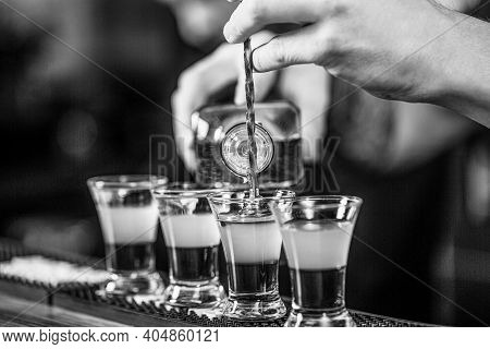 Shots At The Nightclub. Red Cocktail At The Nightclub. Barman Preparing Cocktail Shooter. Bartender