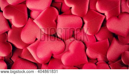 Valentine's Day Background. Holiday Abstract Valentine Background with red satin Hearts. Heart Shape Backdrop. Love concept.