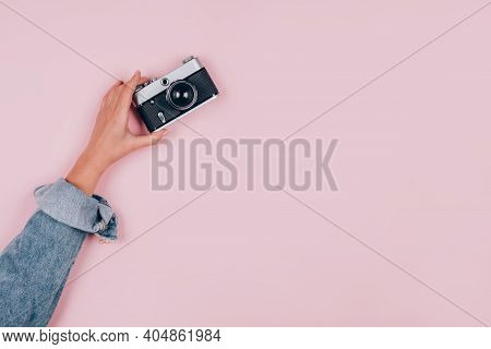 Female Hand Holding Old Vintage Photo Camera On Pink Background With Copy Space For Text. Trendy Vin
