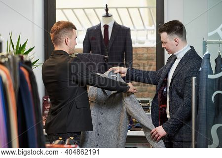 A Young Stylish Man In A White Turtleneck Sweater And A Suit Is Consulting With A Shop Assistant Abo