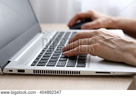 Elderly Woman Working At The Laptop. Wrinkled Female Hands On Notebook Keyboard On A Desk In Sunligh