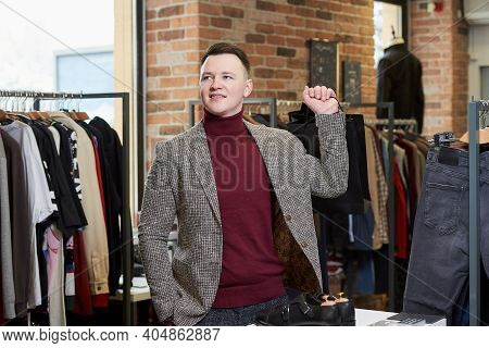 A Young Man In A Sports Jacket Is Waiting With His Purchase In A Clothing Store. A Happy Male Custom
