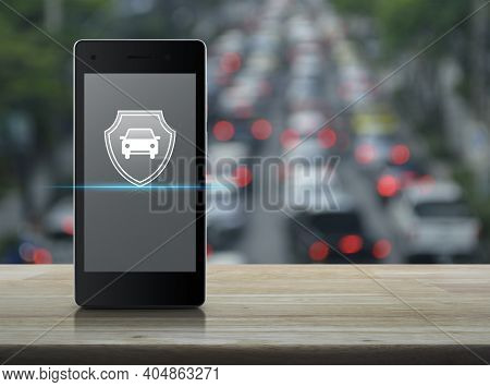 Car With Shield Flat Icon On Modern Smart Mobile Phone Screen On Wooden Table Over Blur Of Rush Hour