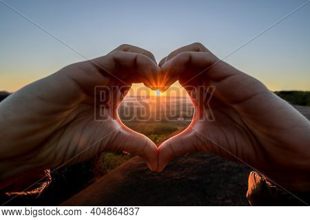 Silhouette Woman Hand In Shape Of Love Heart With Sunrise. Fresh Start Of Valentine's Day.