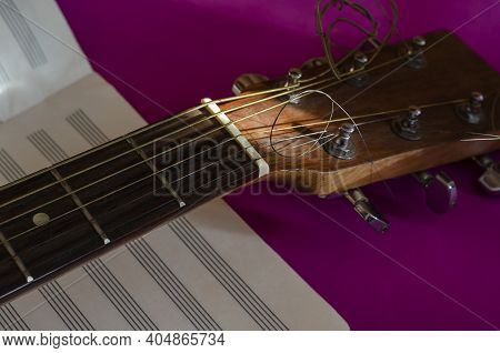 Close-up Of An Acoustic Guitar Fingerboard Head And A Blank Sheet Of Music. Sunlight On A Musical In