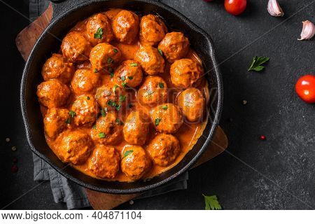 Homemade Meatballs In Tomato Sauce Close Up. Beef Meatballs In Cast Iron Pan On Black Background.