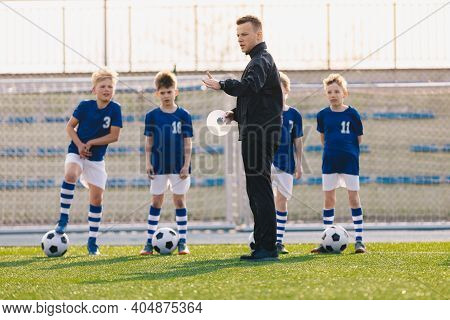 Young Man Soccer Coach Explaining Training Rules To Group Of Children. Boys In Football Team On Outd
