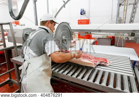 A Worker In Meat Factory, Chopped A Fresh Beef Meat In Pieces On Work Table, Industry Food.