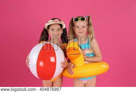 Cute Little Children In Beachwear With Bright Inflatable Toys On Pink Background