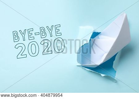 Bye-bye 2020. Torn Paper With Toy Ship Imitating Sinking And Ending Of Year