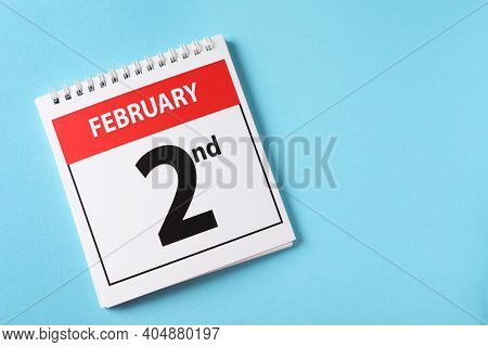 Top View Of Calendar With Date February 2nd On Light Blue Background, Space For Text. Groundhog Day
