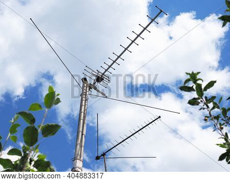 Two External Tv Antennas Stand On Makeshift Poles Against The Backdrop Of Sky And Clouds. Shot In Th