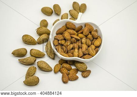 White Faience Cup With Peeled Almonds Next To Untreated Almonds Seeds And Dry Flower On White Backgr