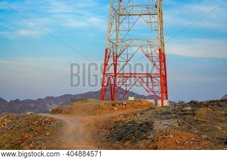 Dirt Road Near A Red & White Mobile Tower On A Hilltop. From Muscat, Oman.