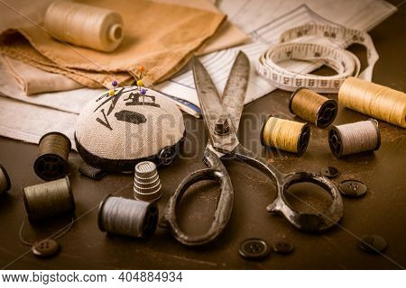 Sewing and craft tools - old scissors, bobbins with thread and needles on wooden table in vintage style